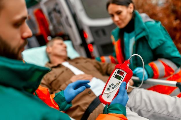 Медработники проверяют уровень кислорода в крови и перевозят каталку пожилого пациента из современной машины скорой помощи для дальнейшей медицинской помощи в клинике.