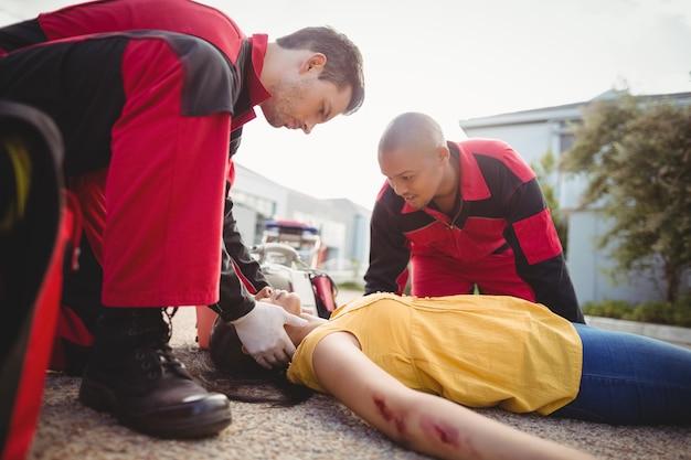 負傷した女性を調べる救急隊員
