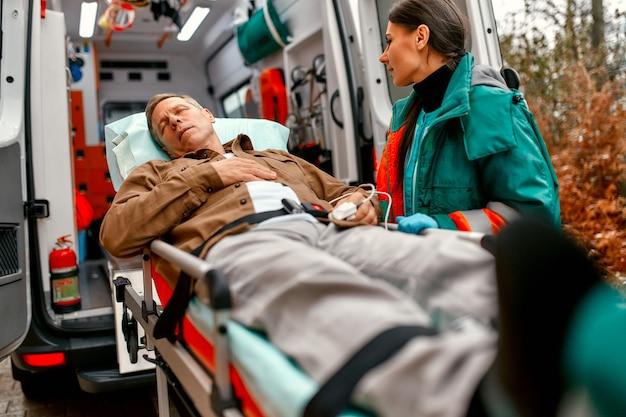Медработники вывозят каталку с пожилым пациентом из современной машины скорой помощи для дальнейшего оказания медицинской помощи в клинике.