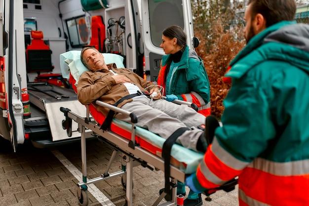 救急隊員は、クリニックでのさらなる医療のために、現代の救急車から高齢の患者と一緒に担架を取り出します。