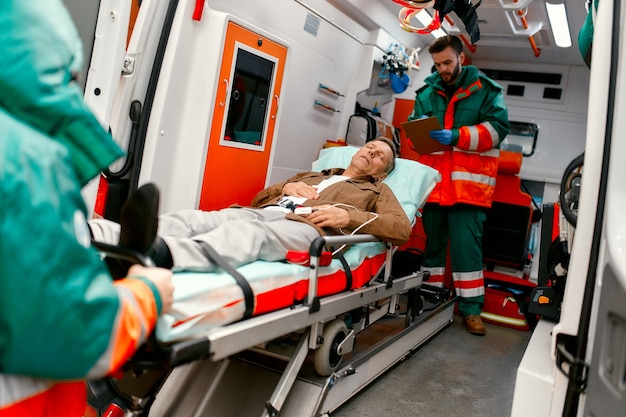 Paramedics take out a gurney with an elderly patient from a modern ambulance for further medical care at the clinic.