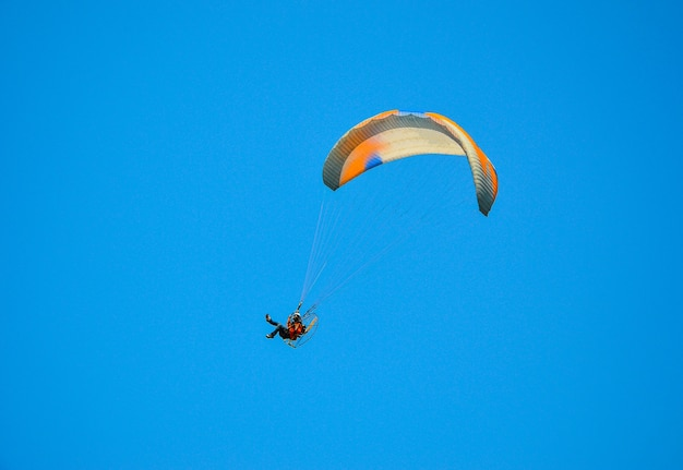 Paramotor flying in the blue sky