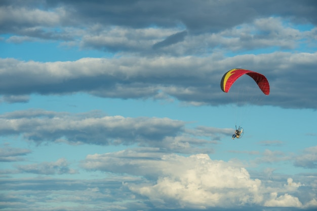 Paramotor flying over the fields in the sky.