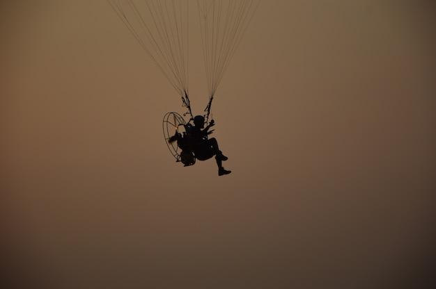 Paramotor flying on sunset background