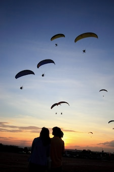 Paramotor or paratrike silhouettes at sunset