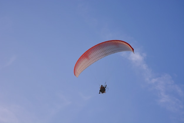 Paramotor (powered paraglider) with red-white parachute flying in sky, extreme sport.