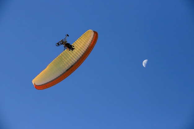 Paramotor in the sky with the moon. Premium Photo