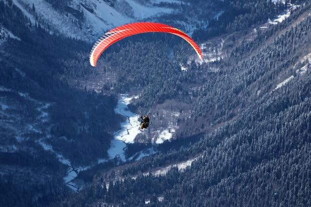 雪に覆われたコーカサス山脈と晴れた青い空の上を飛んでいるパラプレーン