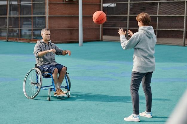 Зрелый мужчина с параличом нижних конечностей в инвалидной коляске бросает мяч женщине, которую они тренируют на спортивной площадке ...
