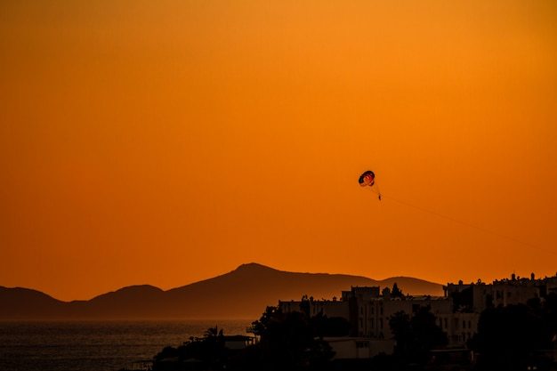 Parasailing on the calm sea at sunset