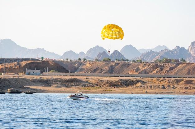 パラセーリングパラシュートアクティブスポーツスカイシーボート。スピードボートが観光客と一緒に黄色いパラシュートを引っ張る。海の観光客のための極端な娯楽。