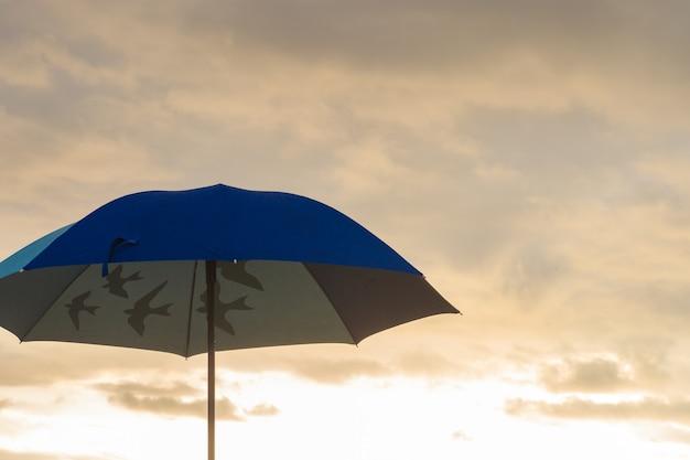 Зонтик на песчаном пляже вдоль моря на рассвете