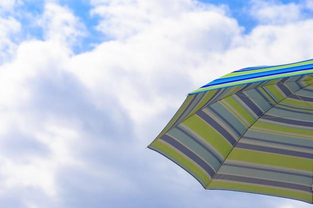 Parasol on a sandy beach along the sea at sunrise.