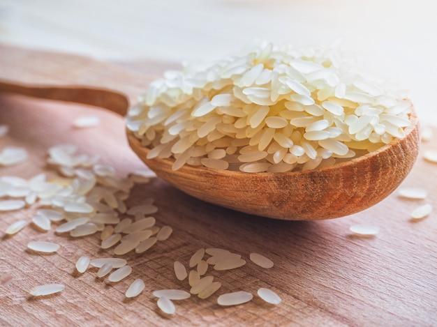 Пропаренный рис и деревянная ложка на деревянном столе.