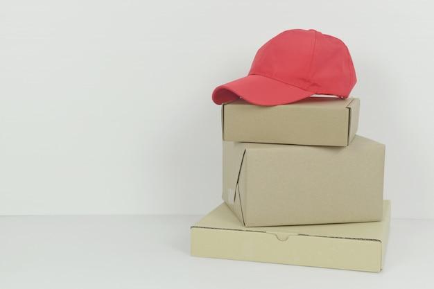 白い背景のコピースペース配信コンセプトに赤い野球帽と小包ボックスピザボックス