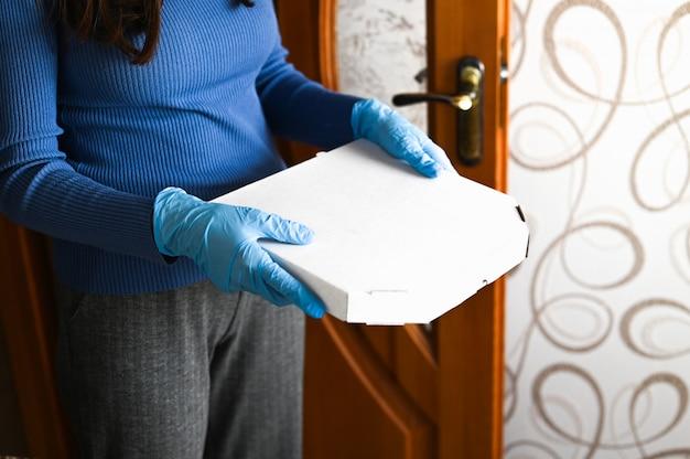 宅配便。新しいコロナウイルス2019-nkov。室内の配達人からパッケージを受け取る医療用マスクを着た若い女性。ウイルス予防