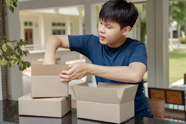 소포 배달 개념은 파란색 티셔츠를 입은 똑똑한 소년이 카운터 바에 있는 온라인 상점에서 소포와 물건을 확인하는 것입니다.