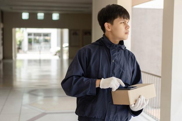 소포 배달 개념 네이비 블루 코트를 입은 젊은 우체부가 자신의 스마트 폰을 사용하여 소포를 보낼 고객의 주소를 찾습니다.