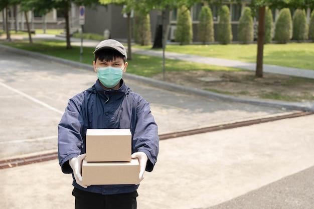 Концепция доставки посылок: молодой отправитель поднимает две коробки с посылками и стоит посреди узкой улицы, чтобы найти здание, в котором он сбросит эти две посылки.
