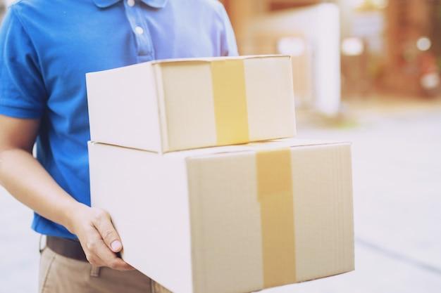 Посылок доставщик посылки через службу отправки на дом. консигнационная рука подача заказа заказчику, принимающему партию коробок от доставщика.