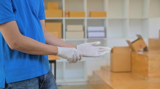 小包配達スタッフは、配達中の感染を防ぐために手袋を着用しています。