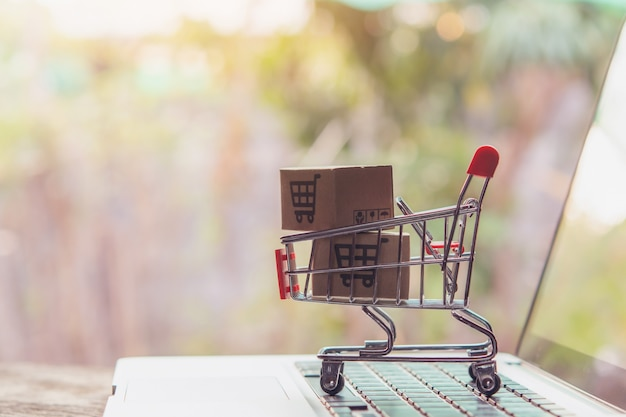 노트북 키보드에 트롤리에 쇼핑 카트 로고가있는 소포 또는 종이 상자. 온라인 웹에서 쇼핑 서비스. 택배를 제공합니다.