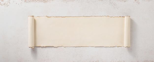콘크리트 벽 표면 배경에서 양피지 스크롤