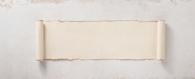 Parchment scroll at concrete wall surface background