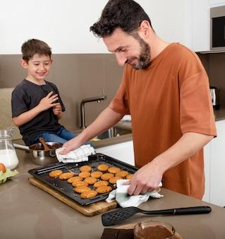 Родитель и мальчик печет печенье