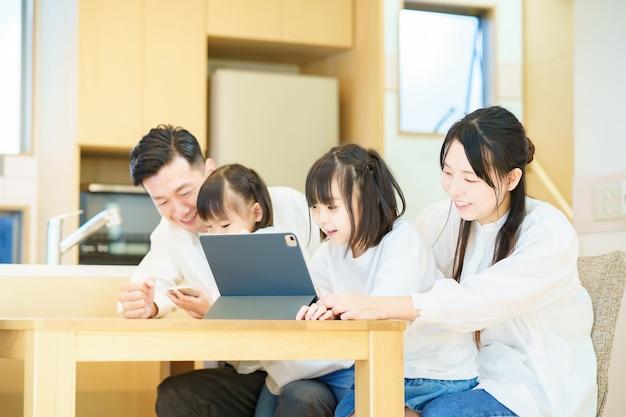Родитель и ребенок, глядя на экран планшетного пк в комнате