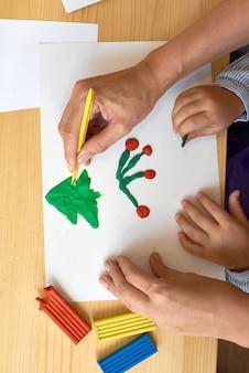 Родитель и ребенок делают рождественские поделки