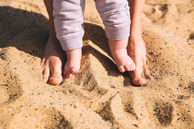裸足で歩く親と子ビーチの砂の上で母と赤ちゃんの足ビーチで家族