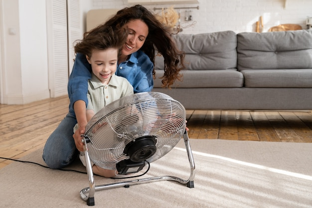 Родитель и ребенок дома веселая молодая мама с маленьким сыном наслаждается дуть прохладным вентилятором в помещении
