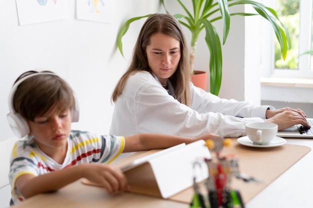 Родитель и ребенок с устройствами средний план