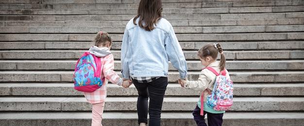 Родитель и ученик начальной школы идут рука об руку. мама двух девочек с рюкзаком за спиной. начало уроков. первый день осени.