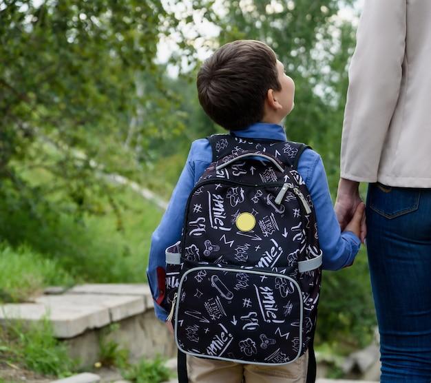 小学校の親と生徒が背中の後ろにバックパックを持って手をつないで行く女性と男の子