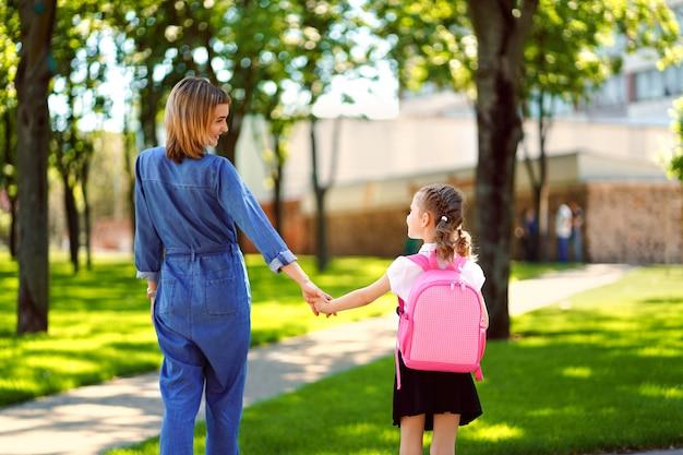 小学校の親と生徒は手をつないで行きます。女性と少女の背中の後ろにバックパック。レッスンの始まり。秋の初日