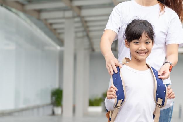 초등학교의 학부모와 학생은 손을 잡고 간다. 뒤에서 배낭을 메고 있는 여자와 소녀. 수업 시작 첫째 날.