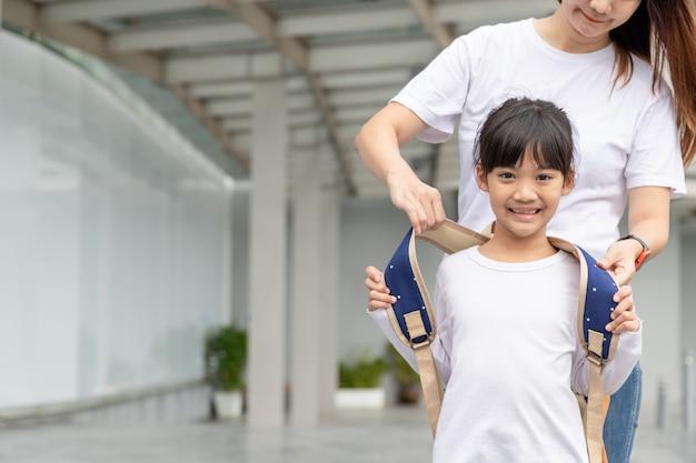 Родитель и ученица начальной школы идут рука об руку женщина и девочка с рюкзаком за спиной
