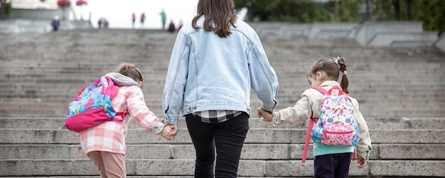 Родитель и ученик начальной школы. мама двух девочек с рюкзаком за спиной. начало уроков. первый день осени.