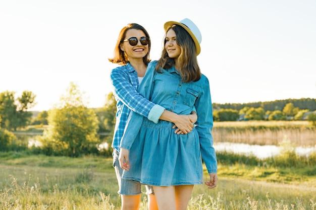 Родитель и подросток, мать и дочь обнимаются, улыбаясь в природе