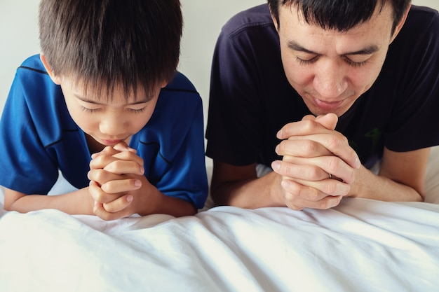 Parent and child praying on the bed