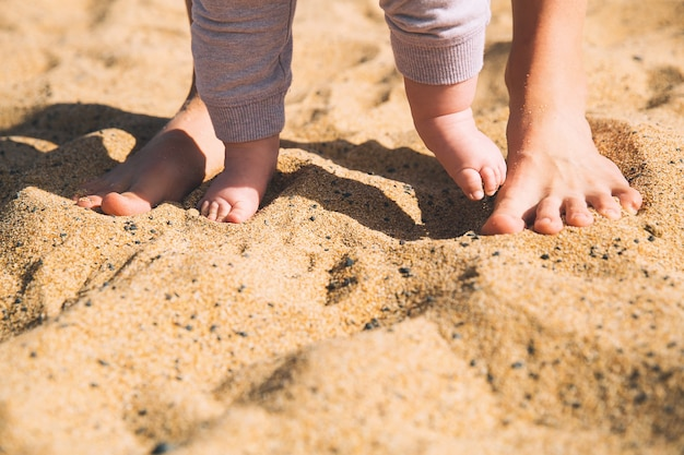 Parent and child walking barefoot mother and cute little baby feet on summer beach sand
