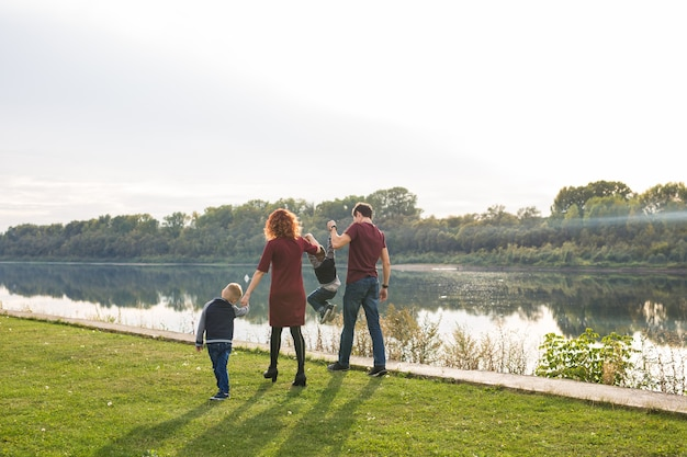 親、子供、自然の概念-水辺で2人の息子と遊ぶ家族。
