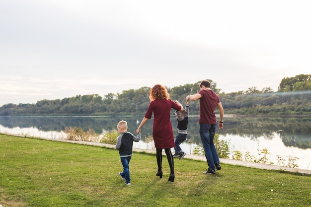 Parent, childhood and nature concept - family playing with two sons by the water.