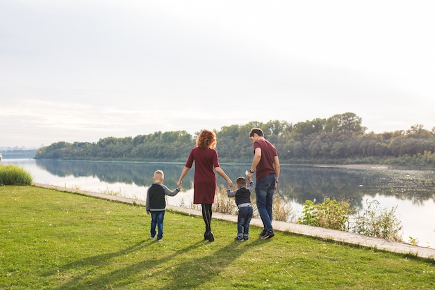 Parent, childhood and nature concept - family playing with two sons by the water