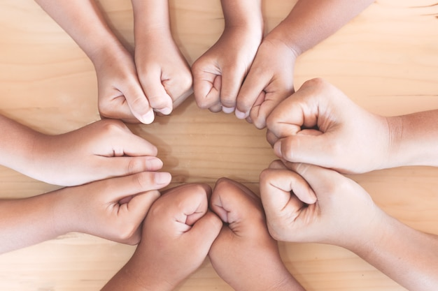 Parent and children fist hands in circle showing unity and teamwork