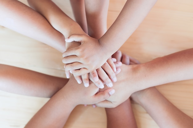 Parent and children holding hands together on wooden background