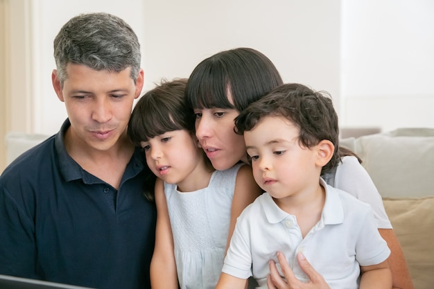 Parent couple and two kids using computer for video call, sitting on couch together, looking at display