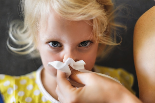 Parent hand helping the little girl to blow her nose with a hygienic wet wipe seasonal sickness